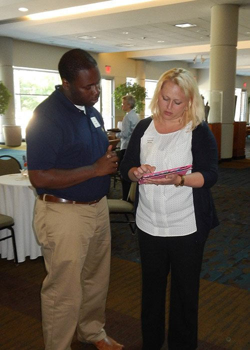 Lauren Miller of Moxley Carmichael demonstrates the site to Ryan Parker, assistant program director for the Wesley House. Maria Cornelius of Moxley Carmichael is in the background discussing the site with another attendee.