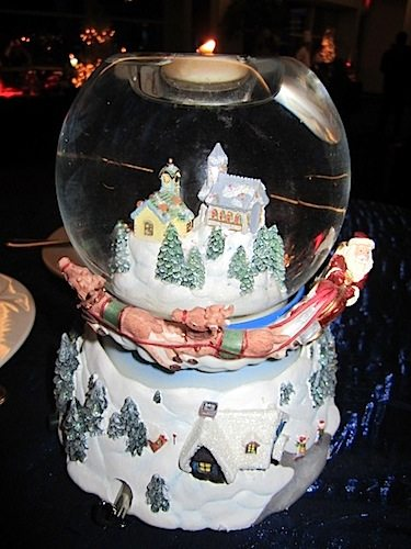 A snow globe as centerpiece provides an enchanting holiday touch to a table.