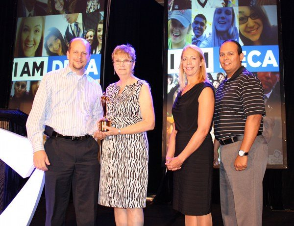 Mike Brown, M&M Productions USA president and CEO, left, presents the Texas Telly Award at DECA's Chartered Association Management Conference to his clients, Sandra Hinesly, Texas DECA executive director; Erica Marshall, Texas DECA board member; and Leo Saenz, Texas DECA board member.